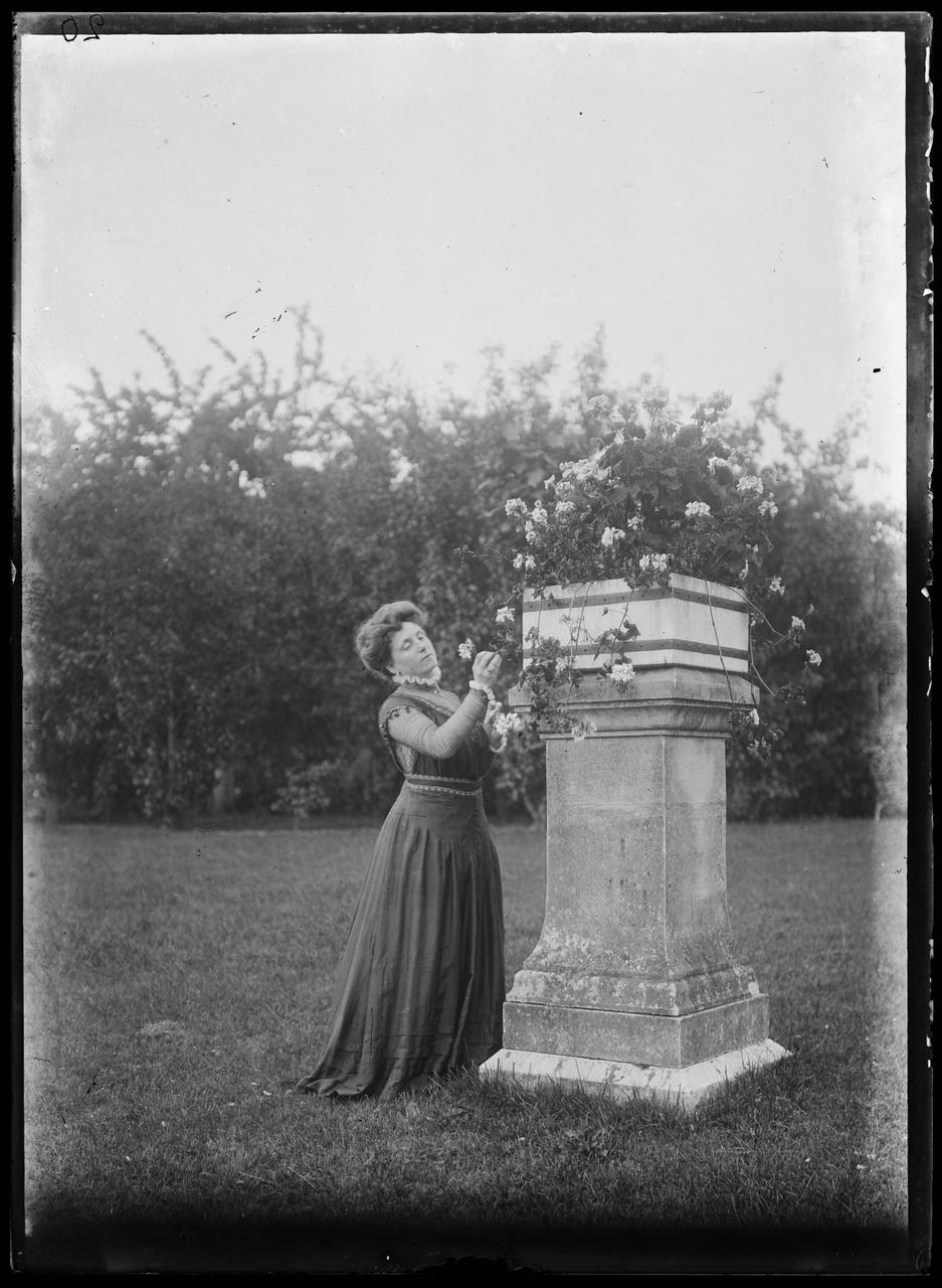 Glasnegatief waarop een vrouw in een tuin is afgebeeld.