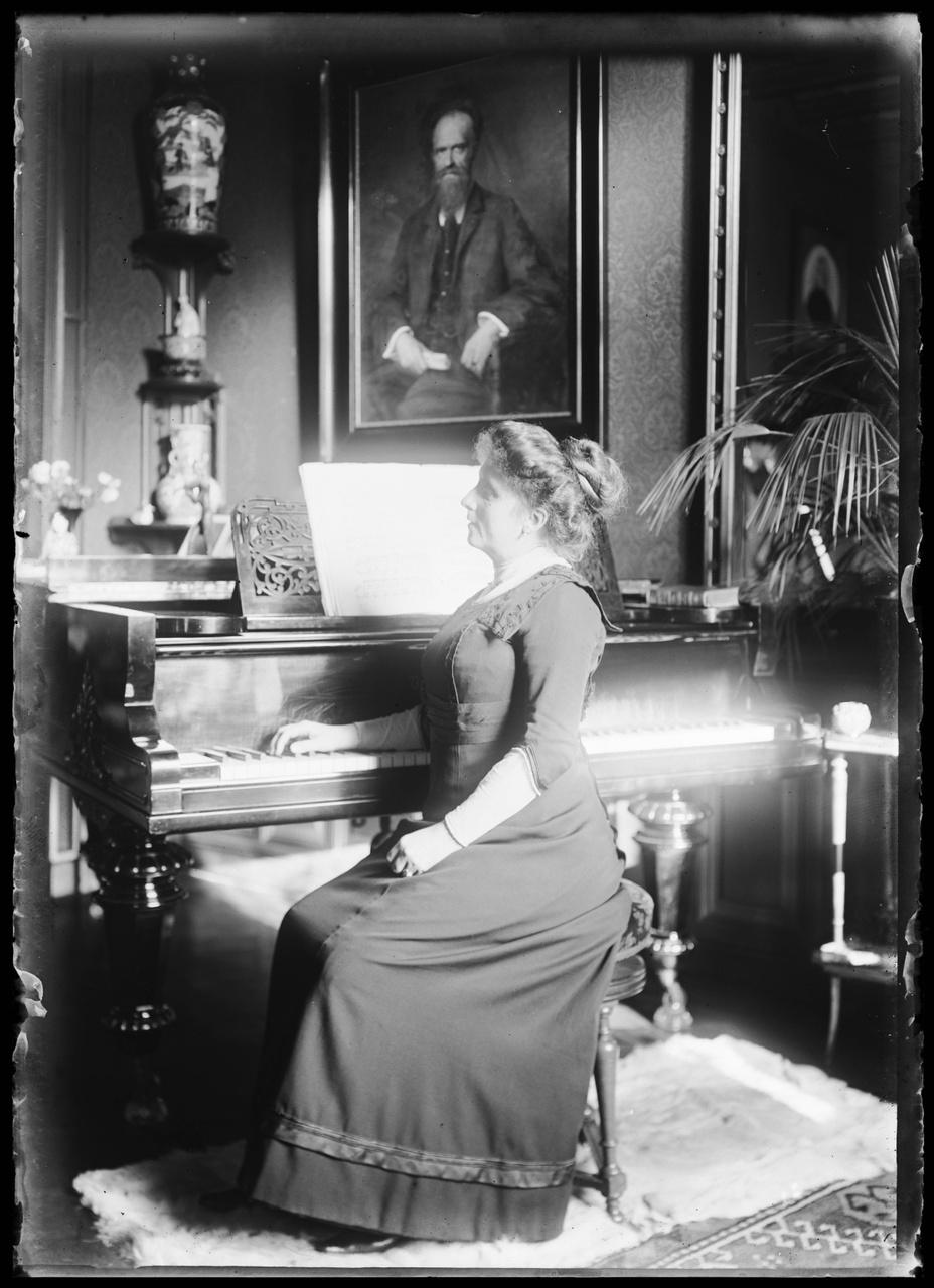 Glasnegatief van Delphine Povel achter piano