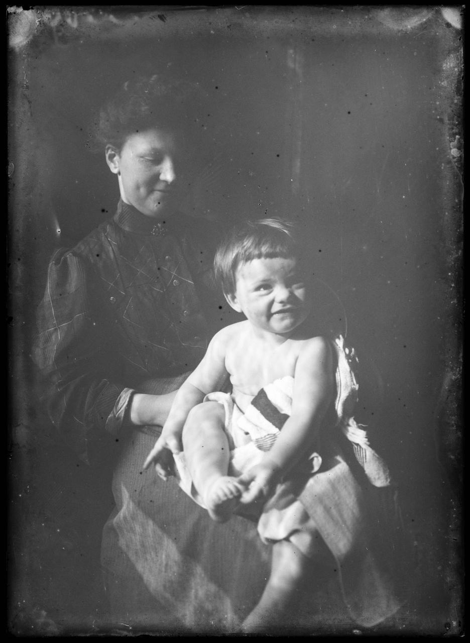 Glasnegatief van familiefoto waarop vrouw met kind