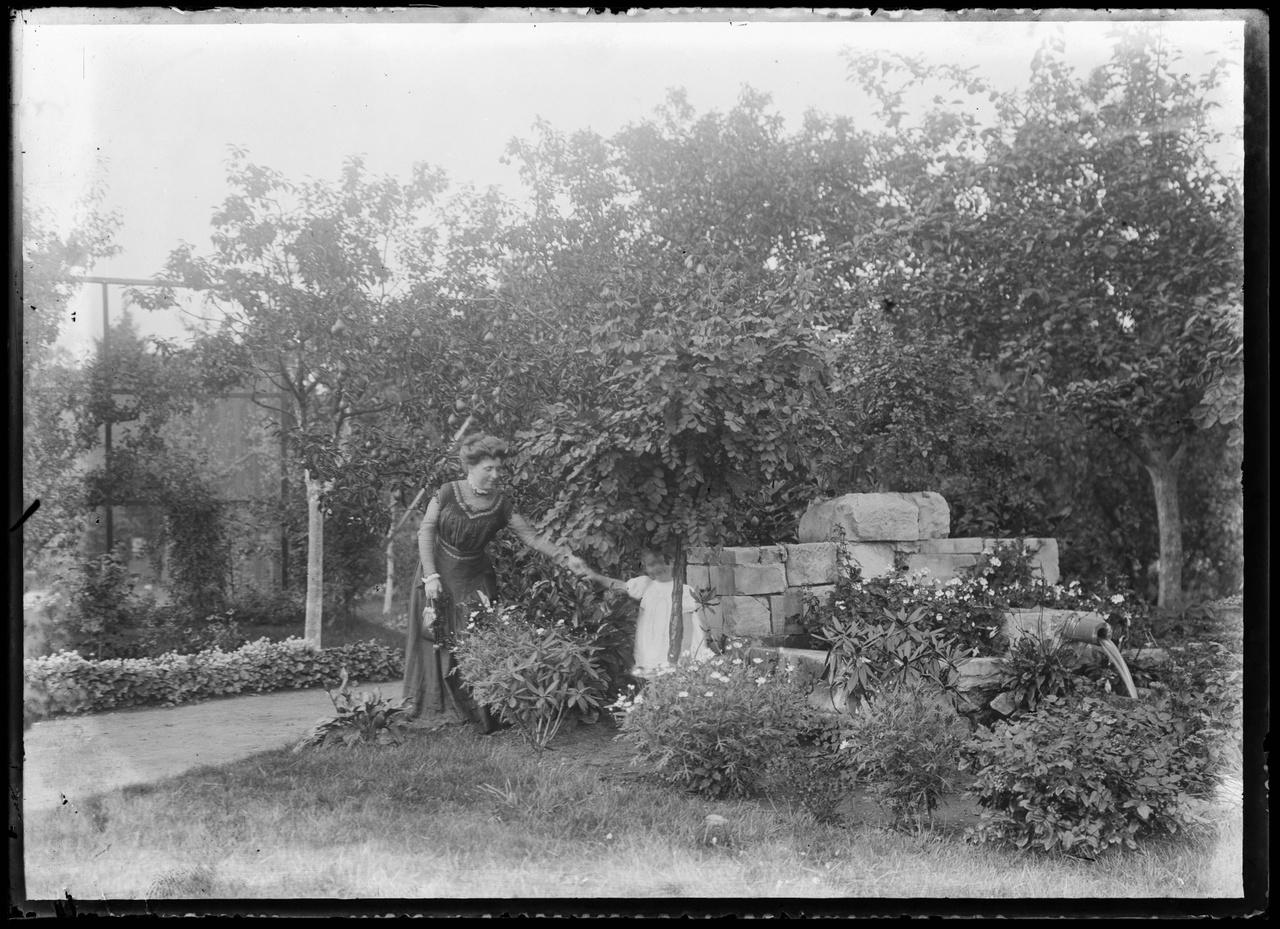 Glasnegatief van familiefoto waarop vrouw met kind in tuin