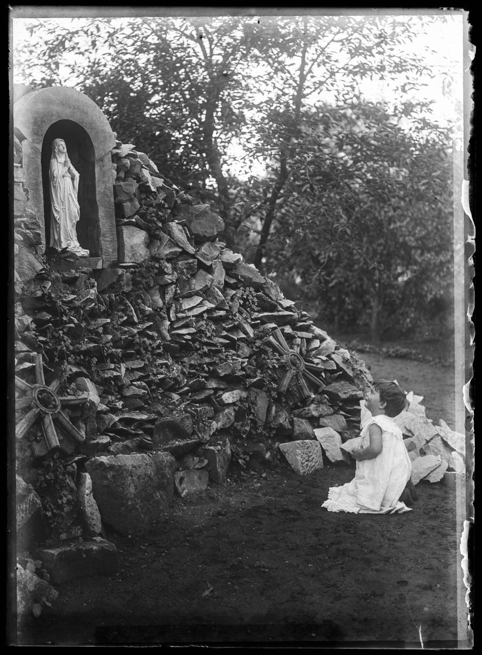 Glasnegatief van een foto van een kind bij een Mariabeeld