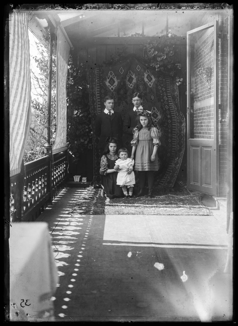 Glasnegatief van een foto van de vijf kinderen van Jos Cuypers in een serre-achtige ruimte.