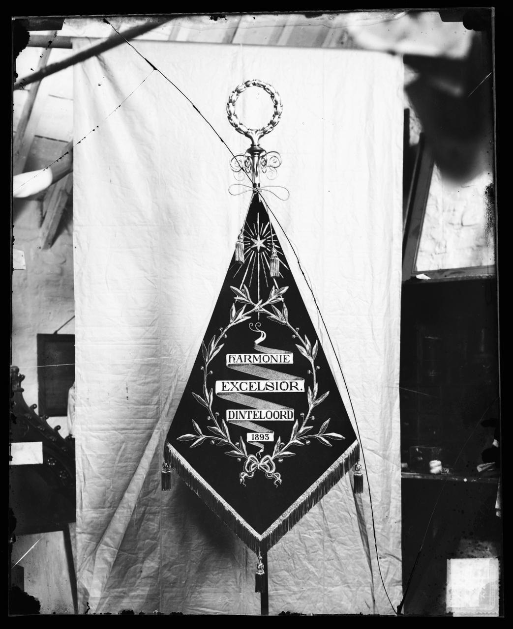 """Glasnegatief van foto van producten uit de Cuypers' Kunstwerkplaatsen uit kist met nummer 23: """"Vaandel Harmonie Excelsior Dinteloord""""."""