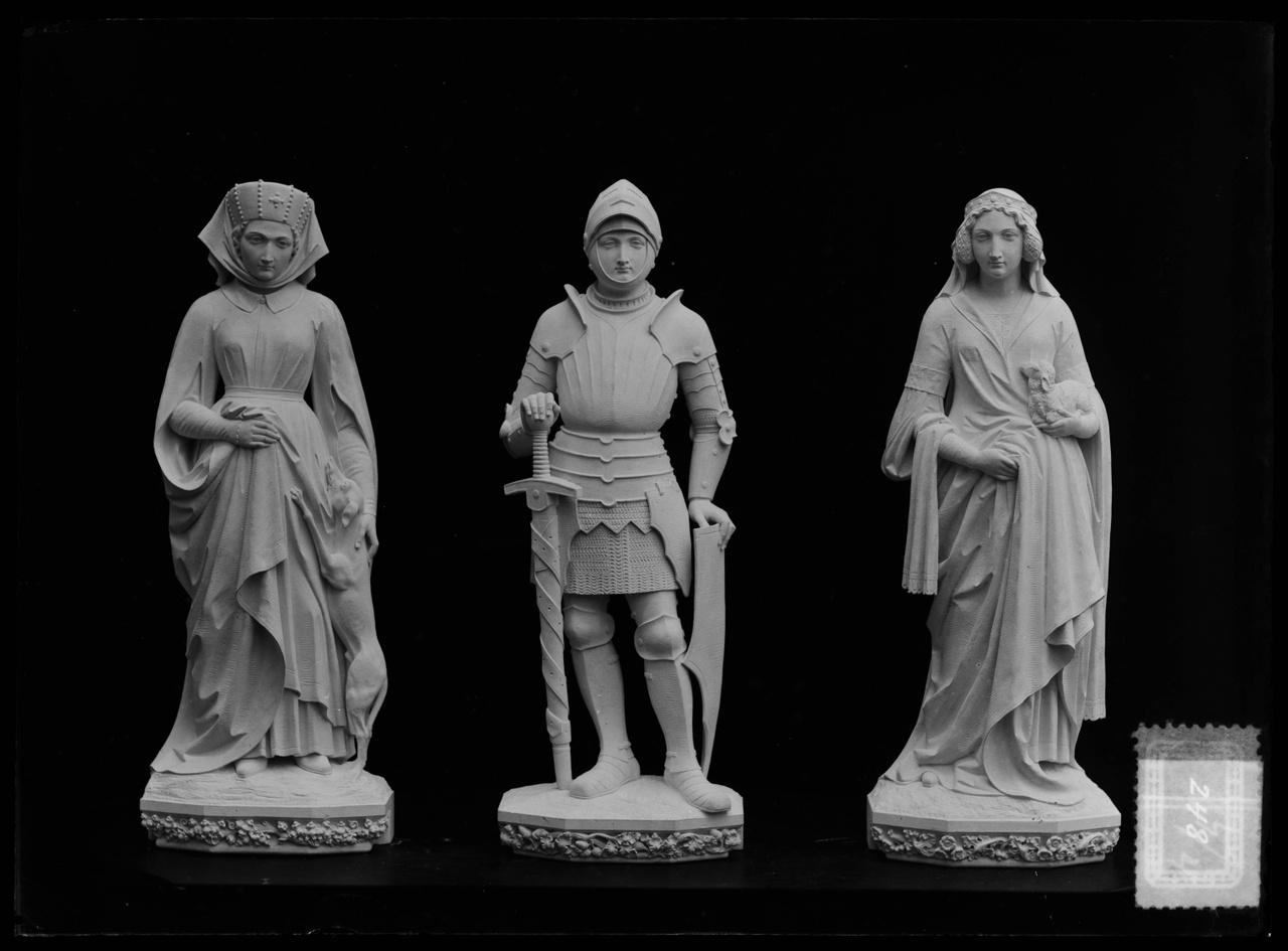"""Glasnegatief van foto van producten uit de Cuypers' Kunstwerkplaatsen uit kist met nummer 24: """"Beelden van een ridder en van twee dames""""."""